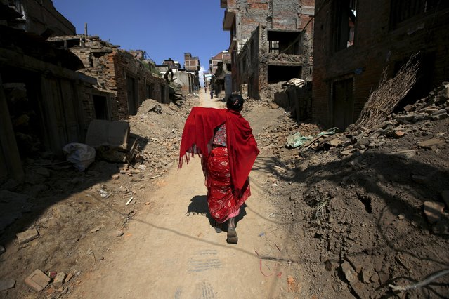 A woman walks past the debris of collapsed houses in Bhaktapur, Nepal October 5, 2015. Twin earthquakes in April and May killed almost 9,000 people in Nepal's worst natural disaster. (Photo by Navesh Chitrakar/Reuters)