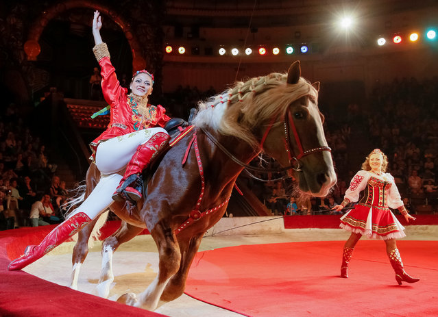 """A horse and its trainers perform during the presentation of the new show """"The extreme arena"""" at the National Circus in Kiev, Ukraine, September 15, 2016. (Photo by Gleb Garanich/Reuters)"""