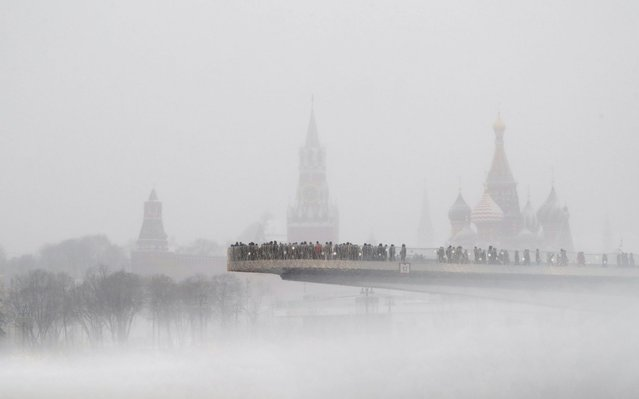 People walk on the floating bridge at the Zaryadye park next to the Spasskaya tower of the Moscow Kremlin and the St. Basil Cathedral during a snowfall day in Moscow, Russia, 04 January 2020. (Photo by Maxim Shipenkov/EPA/EFE/Rex Features/Shutterstock)