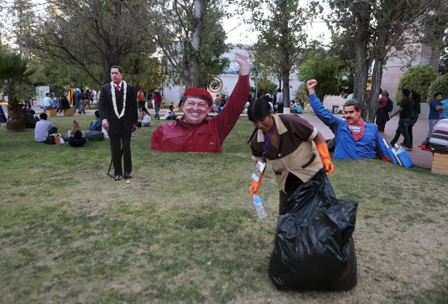 A worker collects garbage in front of images of Venezuela's late President Hugo Chavez (L) and President Nicolas Maduro (R) outside of the World People's Conference on Climate Change and the Defense of Life, ahead of next month's World Climate Change Conference in France, in Tiquipaya, Bolivia, October 10, 2015. (Photo by David Mercado/Reuters)