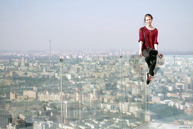 """An astonishing set of snaps of a thrill-seeker's sky-high catwalk show on the edge of some of the world's tallest buildings has turned her into a social media sensation. Daredevil Angelina Nikolau, 23, from Russia, has spent weeks travelling around China and Hong Kong posing for jaw-dropping skyscraper selfies hundreds of feet above the ground. Her vertigo inducing results – uploaded to Instagram – have made her an instant star on the internet. Angelina is described by Russian media as """"self-taught photographer, adventurer and roofer from Moscow"""". Roofing – also known as rooftopping – is where people get as close as possible to the edge of a skyscraper's highest point to take selfies. (Photo by Kirill Oreshkin/CEN)"""