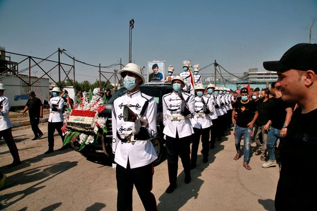 A Military music band and football fans escort the coffin of former Iraqi football star and national team player Nazem Shaker, in the poster at center, who died of COVID-19 during his funeral procession in Baghdad, Iraq, Saturday, September 12, 2020. (Photo by Khalid Mohammed/AP Photo)