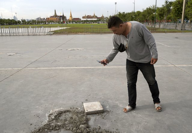 A man takes a picture of a hole at the Sanam Luang field in Bangkok, Thailand, Monday, September 21, 2020. A plaque symbolizing Thailand's transition to democracy has been removed less than 24 hours after it was installed by anti-government demonstrators in a historic royal field. (Photo by Sakchai Lalit/AP Photo)