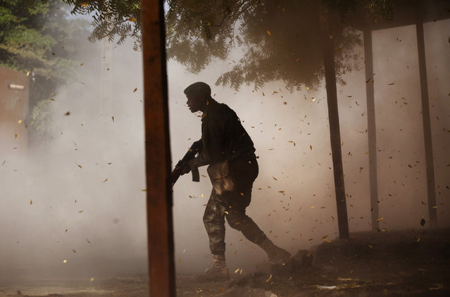 A Malian soldier takes cover amid a cloud of leaves and dust, after a rocket propelled grenade was fired by his comrades in Gao, on February 21, 2013. (Photo by Joe Penney/Reuters/The Atlantic)