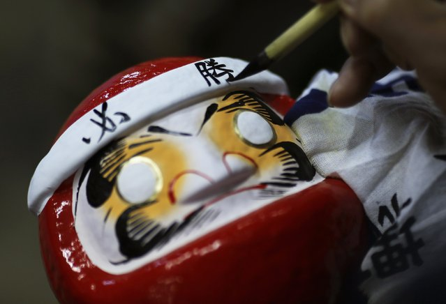 "Japanese craftsman Sumikazu Nakata writes the Chinese character of ""victory"", which is a part of the phrase ""Certain victory"", as he adds the final touches on a Daruma doll, which is believed to bring good luck, at his studio ""Daimonya"" in Takasaki, northwest of Tokyo November 23, 2014. (Photo by Yuya Shino/Reuters)"