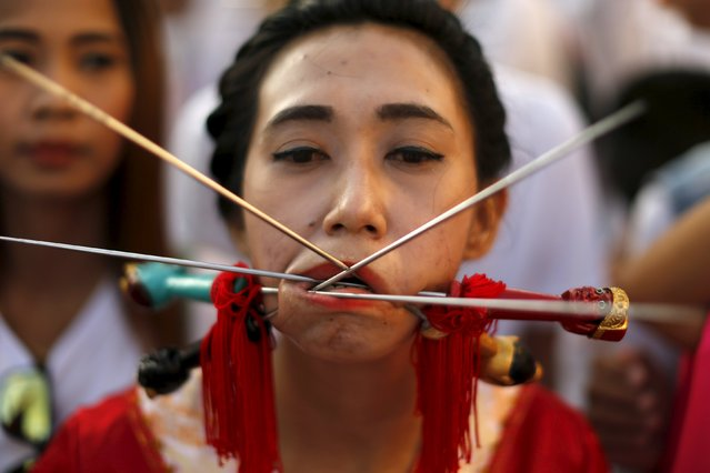 A devotee of the Chinese Jui Tui shrine walks with spikes pierced through her cheeks during a procession celebrating the annual vegetarian festival in Phuket, Thailand October 19, 2015. (Photo by Jorge Silva/Reuters)
