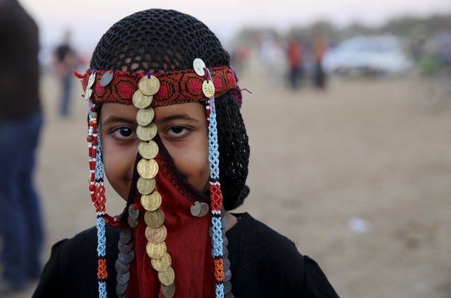 A Palestinian Bedouin girl wears traditional dress and smiles whilst posing for a photo during a heritage and traditional festival activities in Deir el-Balah, central Gaza Strip, Friday, September 16, 2016. (Photo by Adel Hana/AP Photo)