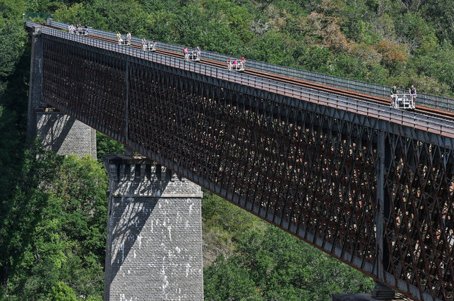 """People cross the Viaduc des Fades as they ride the """"vélorail"""" on an old railway line on August 18, 2020 in Les Ancizes-Comps central France. (Photo by Philippe Desmazes/AFP Photo)"""