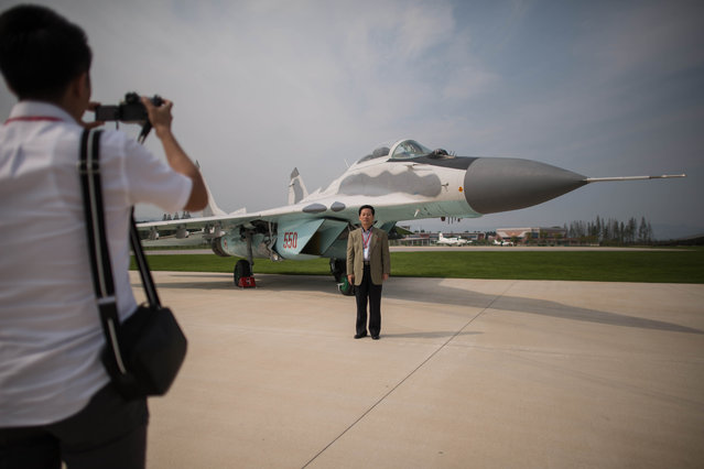A spectator poses for photos before a MiG-29 aircraft during the second day of the Wonsan Friendship Air Festival in Wonsan on September 25, 2016. (Photo by Ed Jones/AFP Photo)