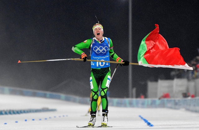 Belarus' Darya Domracheva skis with a Belarus' flag to cross the finish line in the women' s 4x6 km biathlon event during the Pyeongchang 2018 Winter Olympic Games on February 22, 2018, in Pyeongchang. (Photo by Toby Melville/Reuters)