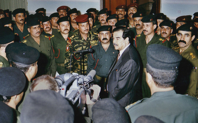 Iraqi President Saddam Hussein, center, talks with elite Republican Guard officers in Baghdad, on March 1, 2003. Iraq began destroying its Al Samoud 2 missiles Saturday as ordered by the United Nations and agreed with weapons inspectors on a timetable to dismantle the entire missile program, U.N. and Iraqi officials said. (Photo by AP Photo/INA/The Atlantic)