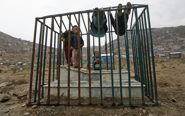 Afghan boys play on a grave at a cemetery in Kabul on March 20, 2013. (Photo by Mohammad Ismail/Reuters)