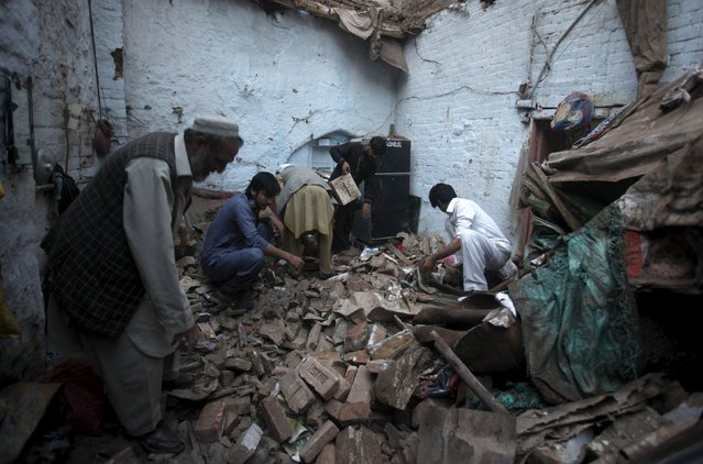 Residents search for belongings in the rubbles of a house after it was damaged by an earthquake in Peshawar, Pakistan, October 26, 2015. A major earthquake struck the remote Afghan northeast on Monday, killing at least 135 people in Afghanistan and nearby northern Pakistan and sending shock waves as far as New Delhi, officials said. (Photo by Fayaz Aziz/Reuters)