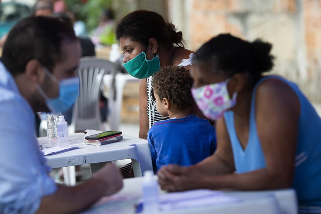 Residents receive medical attention during a campaign organized by doctors and volunteers amid the new coronavirus pandemic in the Chapadao favela in Rio de Janeiro, Brazil, Saturday, October 17, 2020. The residents received health assistance, protective face masks, legal advise and food as part of the campaign. (Photo by Bruna Prado/AP Photo)