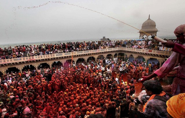 Devotees are smeared with colors and sing at the Nandagram temple, on March 22, 2013. (Photo by Manish Swarup/Associated Press)