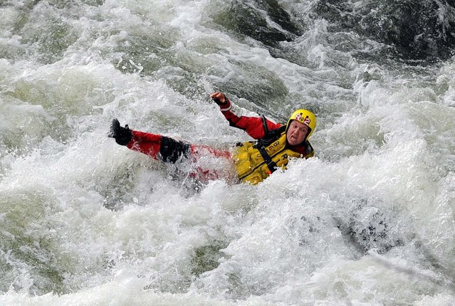 A Bowling Green, Ky., firefighter careens through the rapids of the Barren River after trying to assist in the rescue of two teenage fishermen who were stranded in the rapids after their boat overturned, on April 1, 2013. The fishermen were rescued after two hours and the firefighter was transported to the Medical Center with unknown injuries. (Photo by Joe Imel/Daily News)
