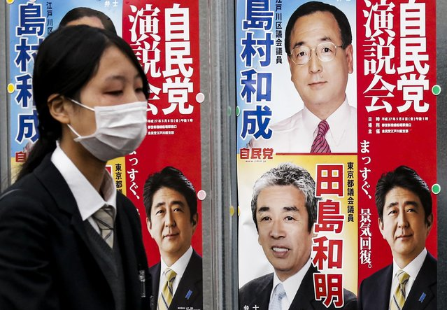 A woman walks past election posters for Japan's upcoming snap election in Tokyo, December 11, 2014. Pictured bottom left and bottom right is Japan's Prime Minister and leader of the ruling Liberal Democratic Party (LDP) Shinzo Abe. (Photo by Thomas Peter/Reuters)