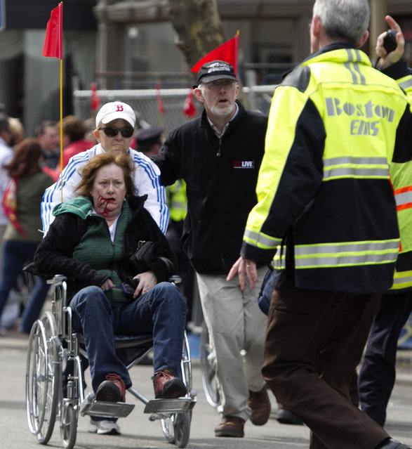 First responders transport an injured woman in a wheelchair where two explosions occurred along the final stretch of the Boston Marathon on Boylston Street in Boston, Massachusetts, U.S., on Monday, April 15, 2013. (Photo by Kelvin Ma/Bloomberg)