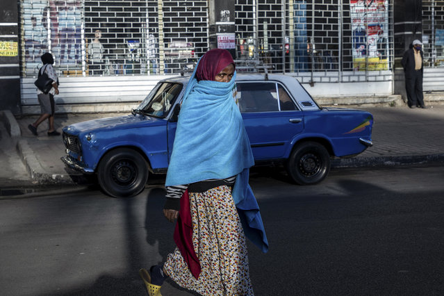 """A woman walks down a street in the capital Addis Ababa, Ethiopia Friday, November 13, 2020. Tensions over the deadly conflict in Ethiopia are spreading well beyond its cut-off northern Tigray region, as the federal government said some 150 suspected """"operatives"""" accused of seeking to """"strike fear and terror"""" throughout the country had been detained. (Photo by Mulugeta Ayene/AP Photo)"""