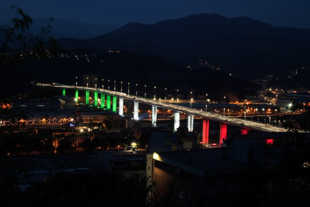 A general view shows the eighteen pillars of the new Genoa bridge illuminated with the colors of the Italian flag, on the eve of the installation of the last part of the scaffolding, in Genoa, northern Italy, 01 August 2020. The new bridge is under construction after the Morandi highway bridge partially collapsed on 14 August 2018, killing a total of 43 people. (Photo by Luca Zennaro/EPA/EFE)