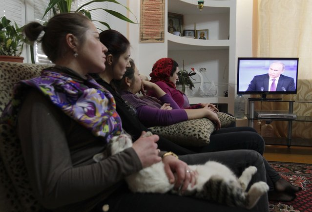 A patient holds a cat while watching a telecast of the annual end-of-year news conference of Russian President Vladimir Putin, with other patients at a rehabilitation centre for drug and alcohol addicts in Stavropol, southern Russia, December 18, 2014. Putin said on Thursday all his actions were aimed at consolidating the Russian society. (Photo by Eduard Korniyenko/Reuters)