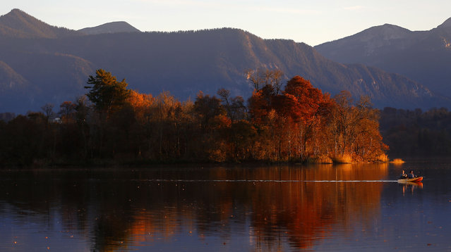 People enjoy the sunny autumn weather at sunset  in a boat on  lake Staffelsee in Uffing near Garmisch-Partenkirchen, Germany, Sunday, November 8, 2015. (Photo by Matthias Schrader/AP Photo)