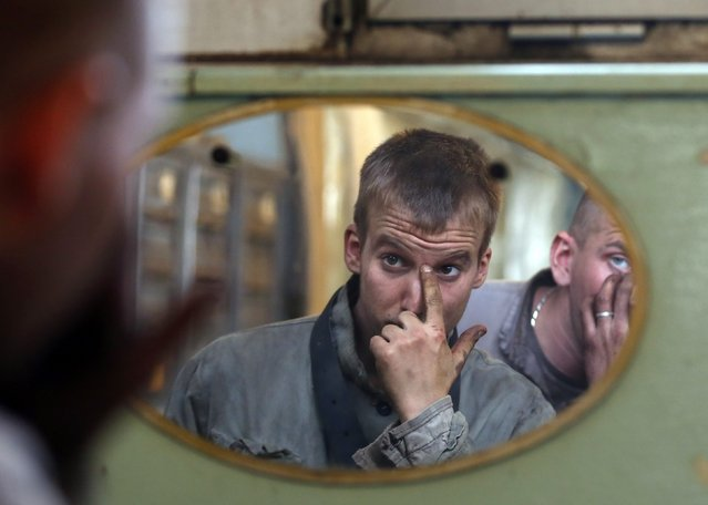 Miners are reflected in the dressing room's mirror after their last working day at Hungary's last hard coal deep-cast mine at Markushegy December 23, 2014. (Photo by Laszlo Balogh/Reuters)
