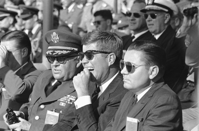 President John  Kennedy watches as airborne troops demonstrate their arsenal of weapons on the firing range on October 12, 1961 at Ft. Bragg, N.C. during a display of their combat readiness. Flanking the chief executive are Gen. George Decker, left, Army Chief of Staff, and Army Secretary Elvis Stahr. (Photo by AP Photo)