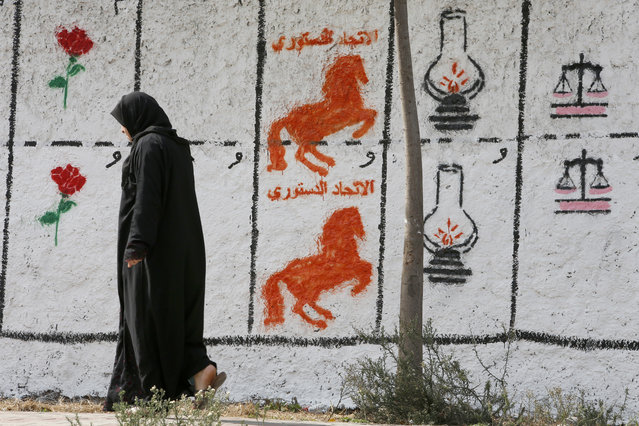 """A Moroccan woman walks past electoral paintings representing a political party logos for the upcoming municipal elections in Casablanca, Morocco, Wednesday, October 5, 2016. Party logos are, from left, are, """"Socialist Union of the People's Forces"""" (Rose), Constitutional Union (horse), """"Justice and Development Party"""" (Lamp) and Party of Istiqlal (Scale) at the Sidi Othmane district of Casablanca. (Photo by Abdeljalil Bounhar/AP Photo)"""