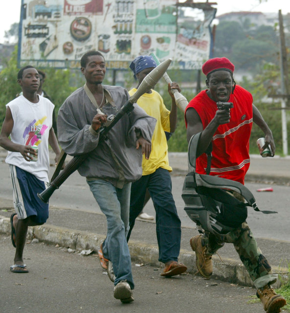 Liberians United for Reconciliation and Democracy (LURD) rebel fighters sing and dance near the main New Bridge in Monrovia August 12, 2003. (Photo by Juda Ngwenya/Reuters)