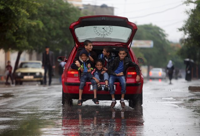 Palestinian schoolboys sit in the trunk of a car as they go to school on a rainy day in Khan Younis, in the southern Gaza Strip, October 7, 2015. (Photo by Ibraheem Abu Mustafa/Reuters)