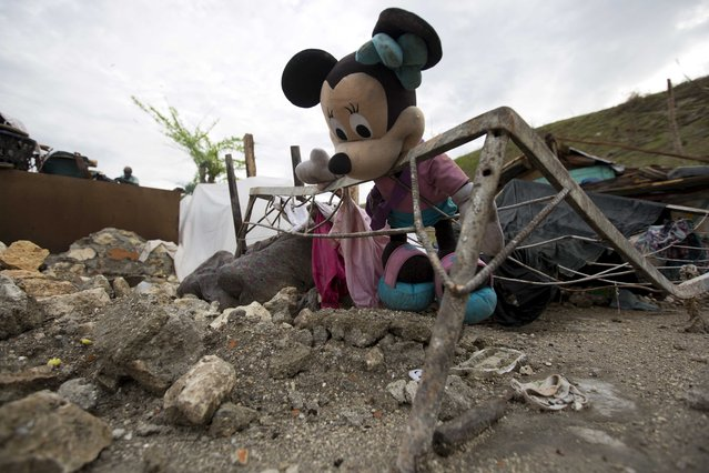 In this Wednesday, October 19, 2016 photo, a Minnie Mouse doll lays inside the frame of a warped iron bed among the debris of a home destroyed by Hurricane Matthew, in Port-a-Piment, a district of Les Cayes, Haiti. While relief can often be slow and chaotic in disasters all around the world, the Western Hemisphere's poorest and least developed country is perennially beset by natural catastrophes and particularly ill-equipped to handle them. (Photo by Dieu Nalio Chery/AP Photo)