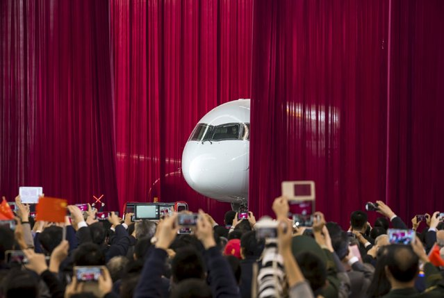 People take pictures and videos as the first C919 passenger jet made by the Commercial Aircraft Corp of China (Comac) is pulled out from behind a curtain during a news conference at the company's factory in Shanghai, November 2, 2015. Comac rolled out China's first homemade 158-seated C919 narrow body jet, which is meant to rival similar models from Airbus Group and Boeing Co. (Photo by Reuters/China Daily)