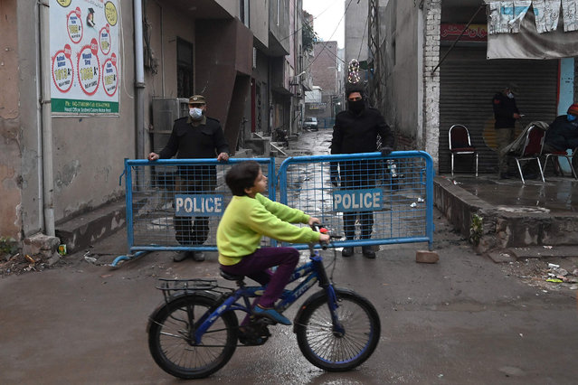 A boy cycles past policemen standing on guard in a cordon off street after authorities sealed the residential area as Covid-19 coronavirus cases continue to rise in Lahore on December 9, 2020. (Photo by Arif Ali/AFP Photo)