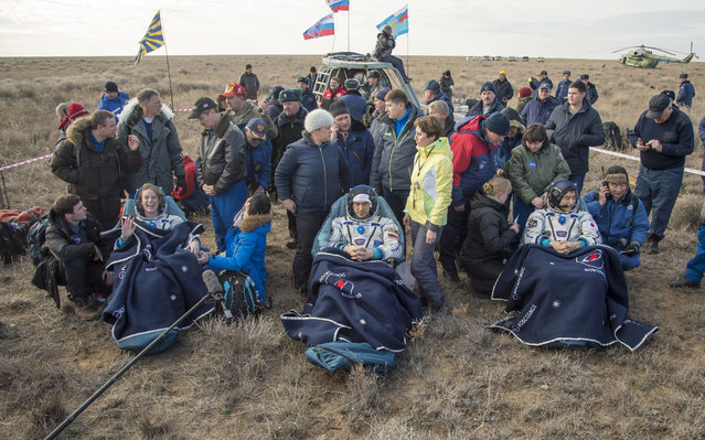 NASA astronaut Kate Rubins, left, Russian cosmonaut Anatoly Ivanishin, center, of Roscosmos and astronaut Takuya Onishi of the Japan Aerospace Exploration Agency (JAXA) sit in chairs outside the Soyuz MS-01 spacecraft just minutes after they landed in a remote area near the town of Zhezkazgan, Kazakhstan Sunday, October 30, 2016. (Photo by Bill Ingalls/NASA via AP Photo)