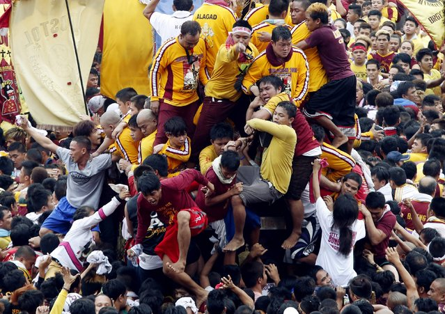 Devotees try to hold the Black Nazarene during an annual procession in Manila, January 9, 2015. (Photo by Erik De Castro/Reuters)
