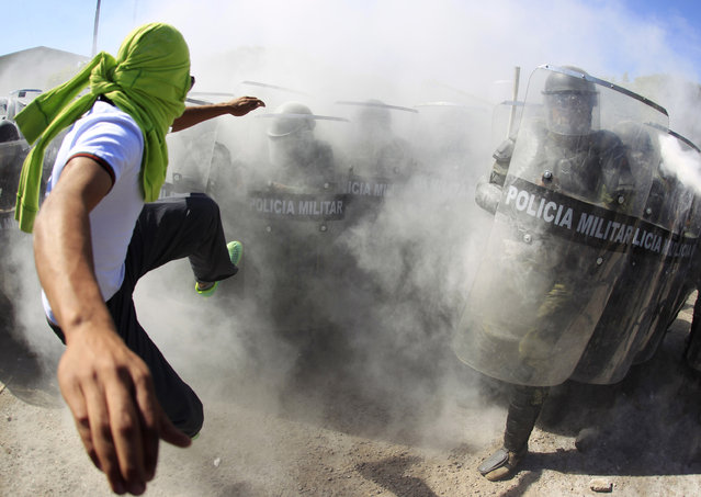 An activist kicks the shields of the military police officers during a demonstration in the military zone of the 27th infantry battalion in Iguala, Guerrero, January 12, 2015. Activists and relatives of the 43 missing trainee teachers from Ayotzinapa's teacher training college broke into the military zone. (Photo by Jorge Dan Lopez/Reuters)