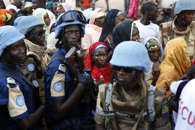 UN soldiers stand near Muslims faithful queuing to enter the Central Mosque on the occasion of Pope Francis visit in Bangui's Muslim enclave of PK5, Central African Republic, Monday November 30, 2015. The Pope was welcomed by a crowd of people and prayed inside the Central Mosque. (Photo by Jerome Delay/AP Photo)