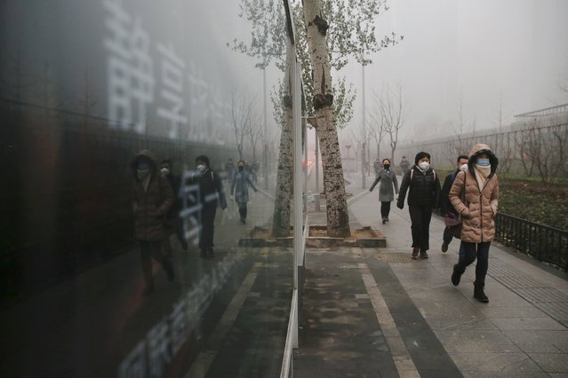People wear protective masks on an extremely polluted morning as hazardous, choking smog continues to blanket Beijing, China December 1, 2015. (Photo by Damir Sagolj/Reuters)