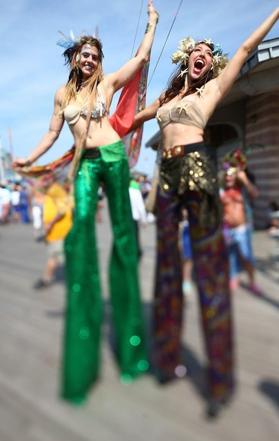 Revelers pose during the 2013 Mermaid Parade at Coney Island June 22, 2013 in the Brooklyn borough of New York City. Coney Island was hard hit by Superstorm Sandy but parade organizers, whose offices were flooded, were able to raise $100,000 on Kickstarter to fund the parade. The Mermaid Parade began in 1983 and features participants dressed as mermaids and other sea creatures while paying homage to the former tradition of the Coney Island Mardi Gras which ran annually in the early fall from 1903-1954.  (Photo by Mario Tama/Getty Images)