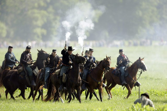 Mounted Union reenactors takes part in a demonstration of a battle during ongoing activities commemorating the 150th anniversary of the Battle of Gettysburg, Friday, June 28, 2013, at  at Bushey Farm in Gettysburg, Pa.  Union forces turned away a Confederate advance in the pivotal battle of the Civil War fought July 1-3, 1863, which was also the war s bloodiest conflict with more than 51,000 casualties. (Photo by Matt Rourke/AP Photo)