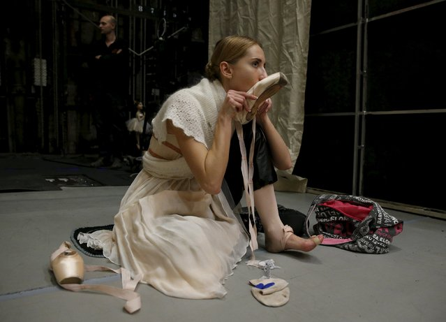 """Ballet soloist Valeria Zapasnikova blows into one of her pointe shoes to warm it up before a rehearsal of """"The Nutcracker"""" choreographed by Nacho Duato at the Mikhailovsky Theatre in St. Petersburg, Russia November 20, 2015. (Photo by Grigory Dukor/Reuters)"""