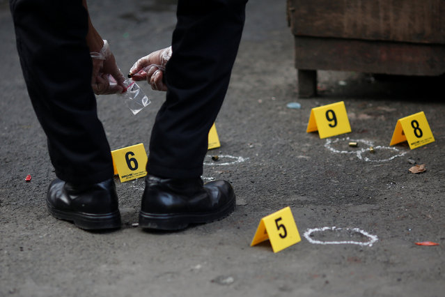 A policeman investigates near the body of a woman killed by unknown gunmen at the market in a port area of Manila, Philippines October 28, 2016. (Photo by Damir Sagolj/Reuters)