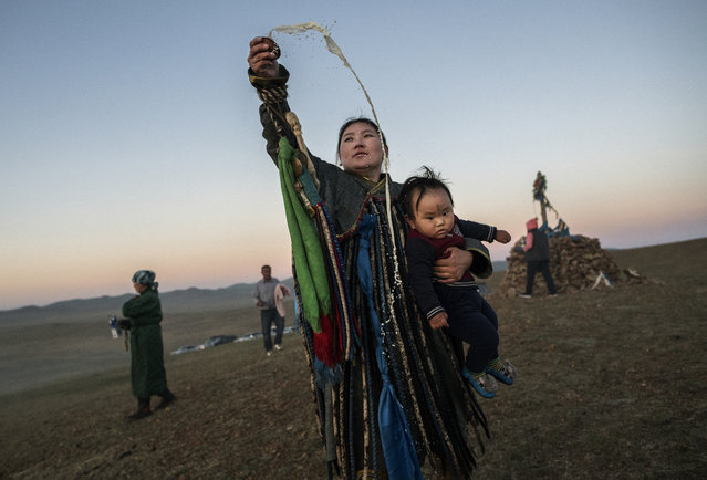 A Mongolian Shaman or Buu, holds her child while throwing milk as an offering during a sun ritual ceremony to mark the period of the Summer Solstice in the grasslands at sunrise on June 22, 2018 outside Ulaanbaatar, Mongolia. (Photo by Kevin Frayer/Getty Images)