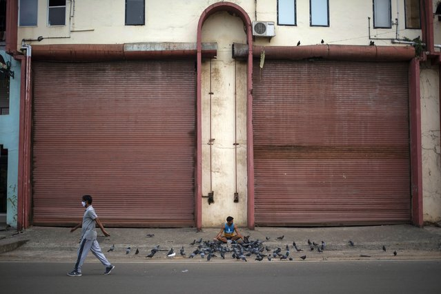 A man wearing a face mask walks past a man feeding pigeons outside the Jawaharlal Nehru stadium in Kochi, Kerala state, India, Tuesday, February 16, 2021. Experts are considering if variants may be driving a surge in cases in the the southern state of Kerala, which had previously been hailed as a blueprint for tackling the virus. Kerala now accounts for nearly half of India's current COVID-19 cases. (Photo by R.S. Iyer/AP Photo)