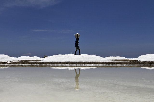 A worker carries salt before loading it onto a supply truck at a salt pan on the eve of May Day or Labour Day on the outskirts of the southern Indian city of Chennai April 30, 2014. India is the third largest salt producing country in the world after China and U.S. with global annual production about 230 million tonnes, according to government data. (Photo by Reuters/Babu)