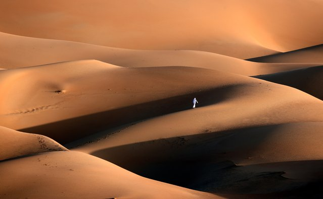 An Emirati youth plays in the sand dunes in the Liwa desert, some 250 kilometres west of the Gulf emirate of Abu Dhabi on January 9, 2021. (Photo by Karim Sahib/AFP Photo)