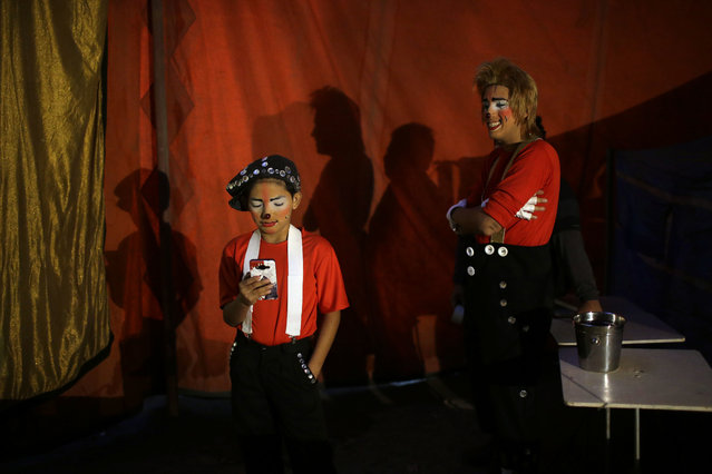 """In this July 20, 2018 photo, clowns Joshep Balta, or """"Cachupito"""", left, and Bryan Jara, or """"Fideito Mix"""" wait to open their show at the International Circus set up in the shantytown of Pro on the outskirts of Lima, Peru. Circus workers say the word 'clown' is used incorrectly in Peru, and understood as a pejorative. (Photo by Martin Mejia/AP Photo)"""