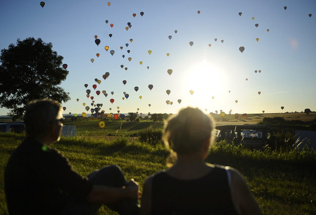 "People watch hot-air balloons fly over Chambley-Bussieres, eastern France, on July 31, 2013, to try to set a world record with 408 balloons in the sky, as part of the yearly event ""Lorraine Mondial Air Ballons"", an international air-balloon meeting. (Photo by Jean-Christophe Verhaegen/AFP Photo)"