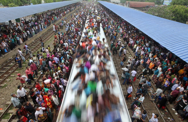 Bangladeshi Muslims travel on the roof of a train to head home ahead of Eid al-Fitr as others wait at a railway station in Dhaka, Bangladesh, Thursday, August 8, 2013. Hundreds of thousands of people working in Dhaka to make a living return home to spend time with their family during Eid al-Fitr. (Photo by A.M. Ahad/AP Photo)